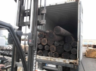 wooden poles loaded into 40ft containers